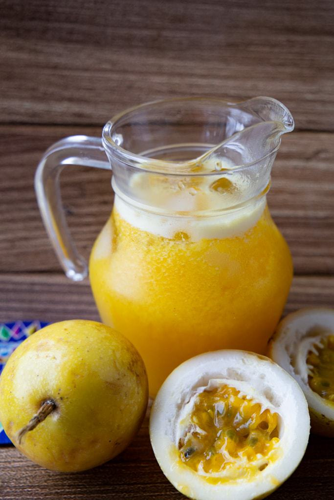 Pitcher of homemade passion fruit juice beside halved passion fruits.
