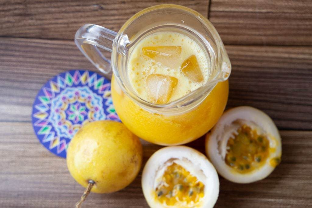 Aerial shot of a pitcher of passion fruit juice on a wooden table.