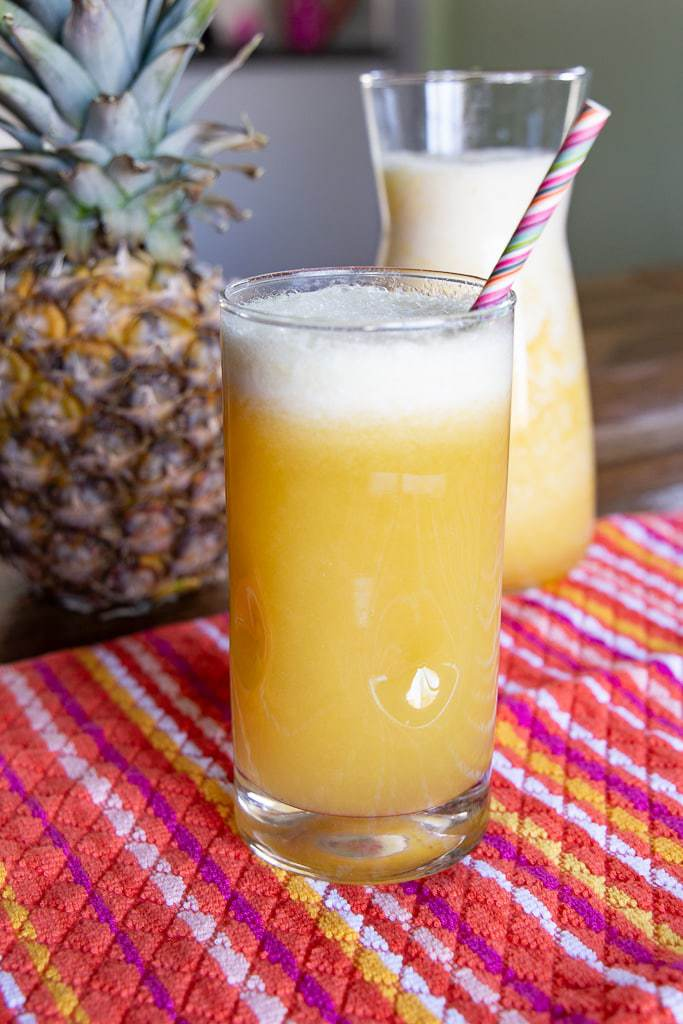 Fresh pineapple juice with a purple striped straw and a whole pineapple fruit in the background.
