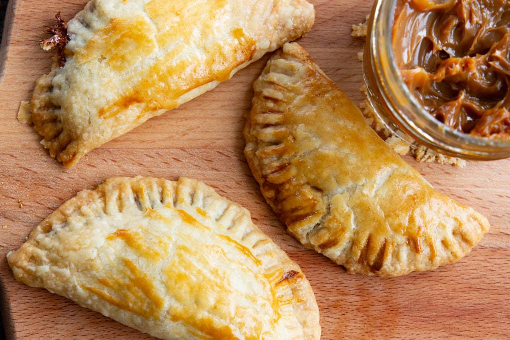 Close up of three freshly baked empanadas beside a jar of cajeta.