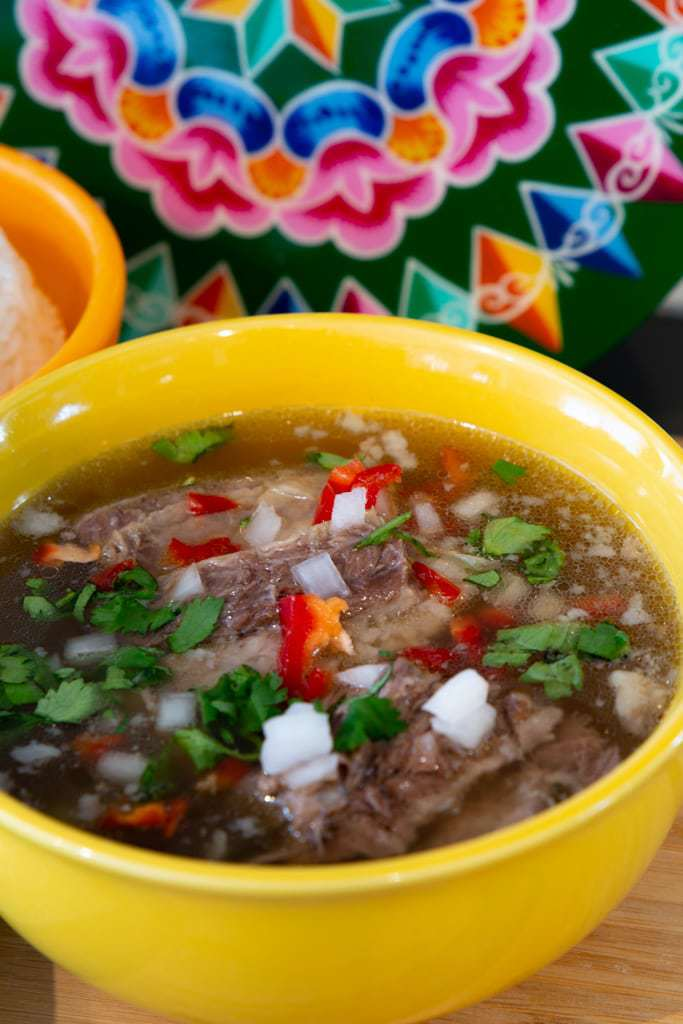 Yellow ceramic bowl full of beef soup with peppers, onions, and cilantro.