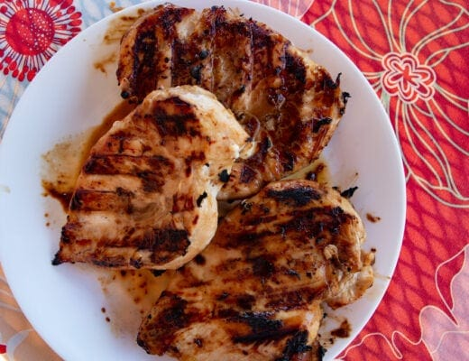 White platter with three grilled chicken breasts heaped on top.