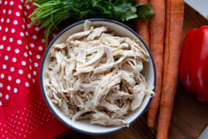 Bowl of shredded chicken flanked by a bunch of cilantro, carrots, a cloth, and a red pepper.