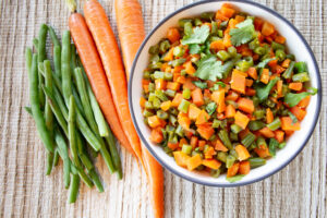 Bundles of carrots and green beans alongside a bowl of finely chopped carrots and beans.