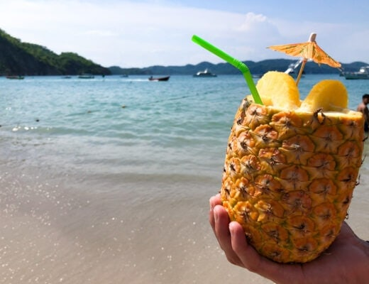 Pina colada in a hollowed out pineapple with the beach in the background.