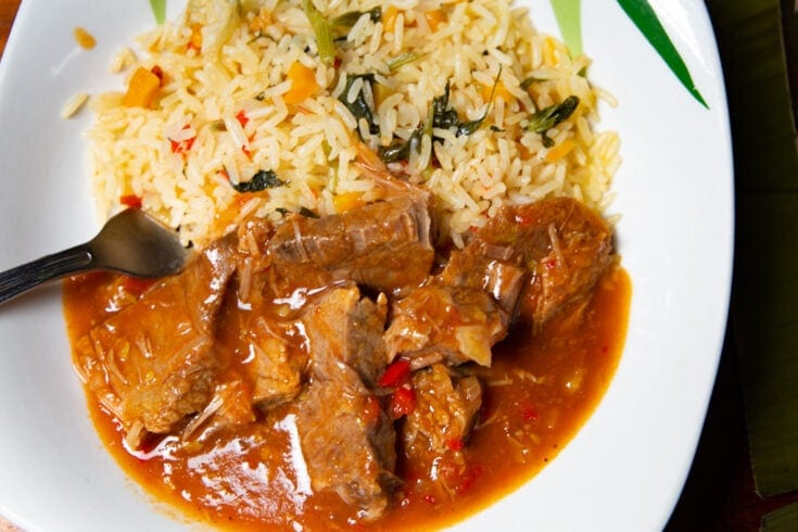 Platter consisting of meat in thick brown sauce and rice.