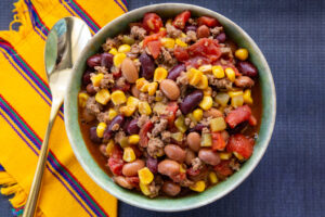 Hearty serving of taco soup with yellow and blue place mats underneath it.