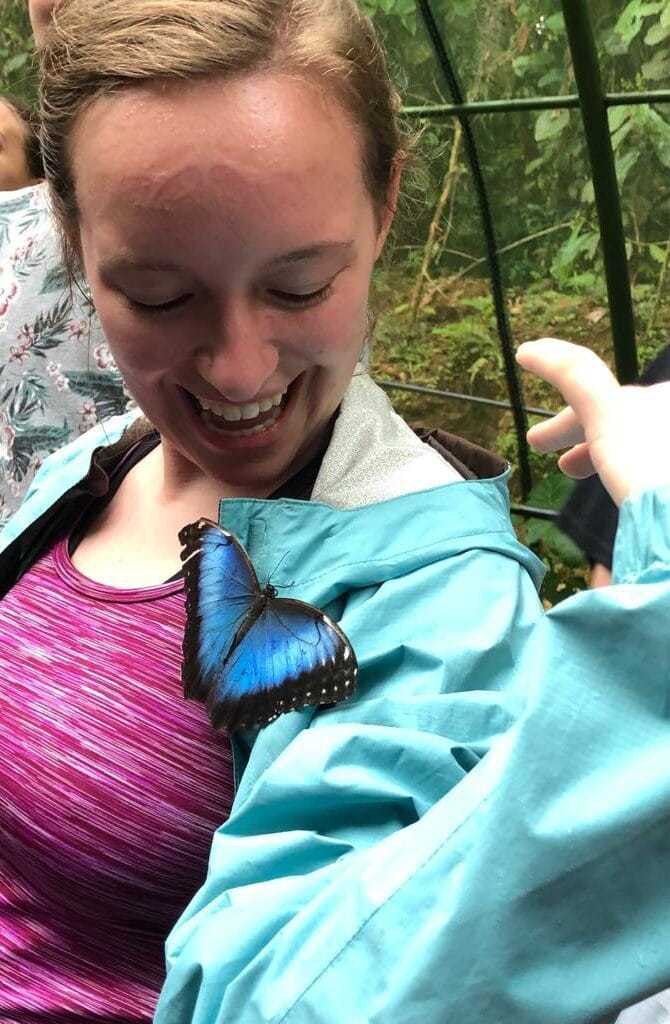 Young woman with a morpho butterfly perched on her jacket.