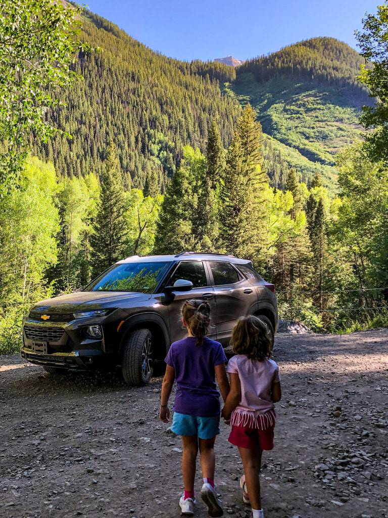 two young girls walking towards a tan 2021 chevrolet trailblazer in the mountains of colorado