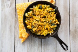 Cast iron pan full of diced squashes and corn placed on top of a folded yellow napkin.