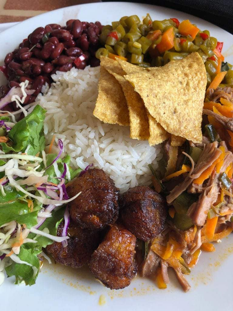 Mound of white rice ringed by fried plantains, beans, meat, picadillo, and salad on a white platter.