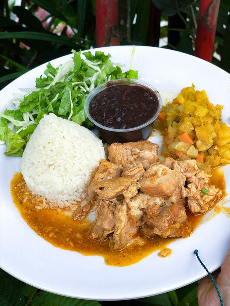 Large white plate with portions of white rice, chicken, picadillo, salad, and black beans.