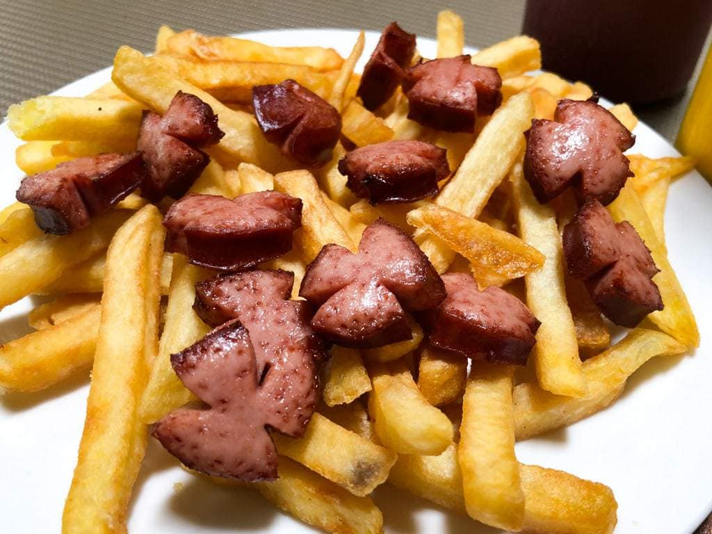 Hot dog sections on a bed of french fries.