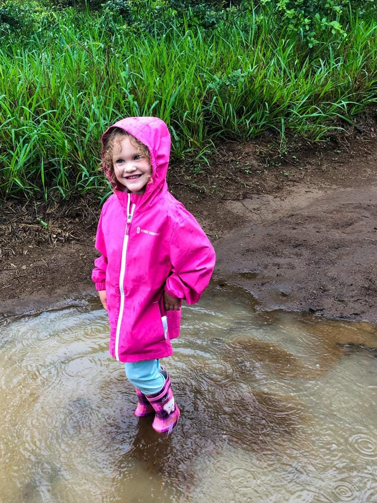 young girl in rain boots stomping in mud puddle in costa rica