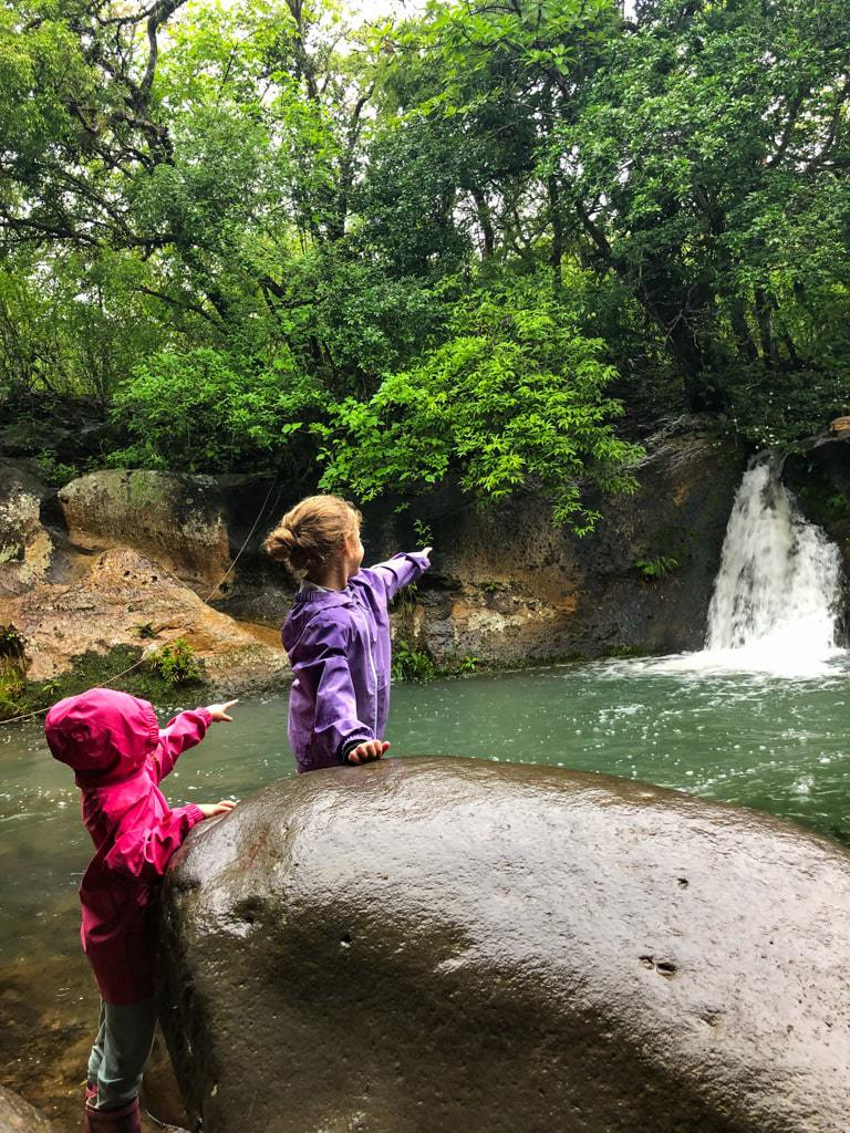 two young girls pointing to a costa rican waterfall in a rainstorm