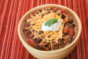 turkey chili in yellow bowl with cheddar cheese and sour cream toppings