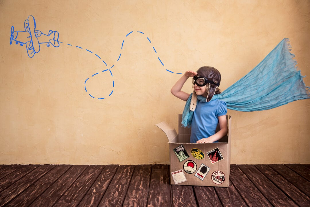 imaginative young child at play looking at an imaginary airplane wearing a cape, aviation hat and goggles in a box with stickers