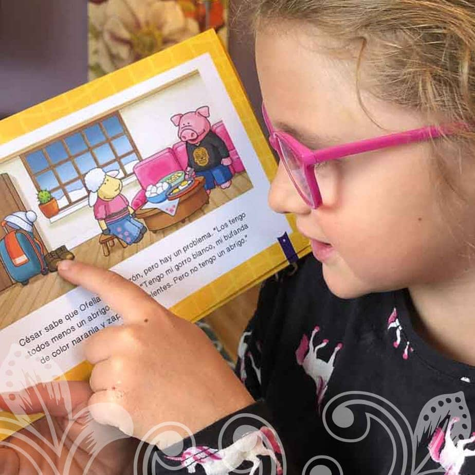 A young girl in glasses reading a book.