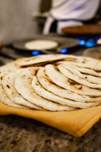 The tortillas laid out on top of each other on a dark wooden table.