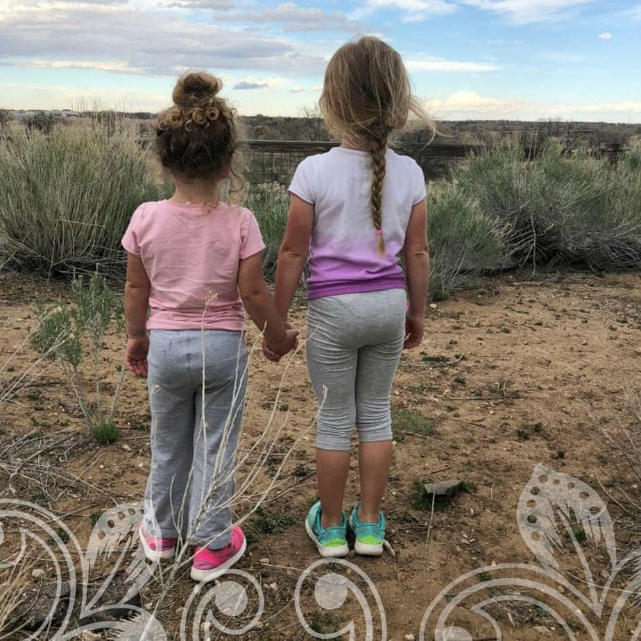 Two young girls standing on a hill.