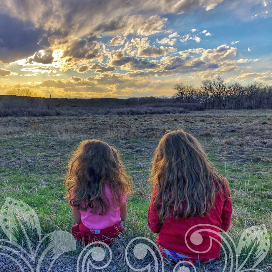 Two children sitting in a field on a cloudy day.