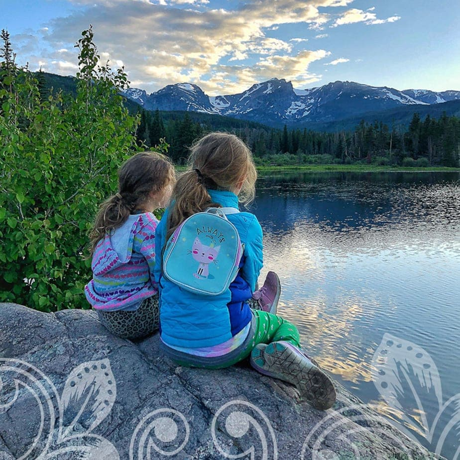 Two young girls sitting on a rock cliff.