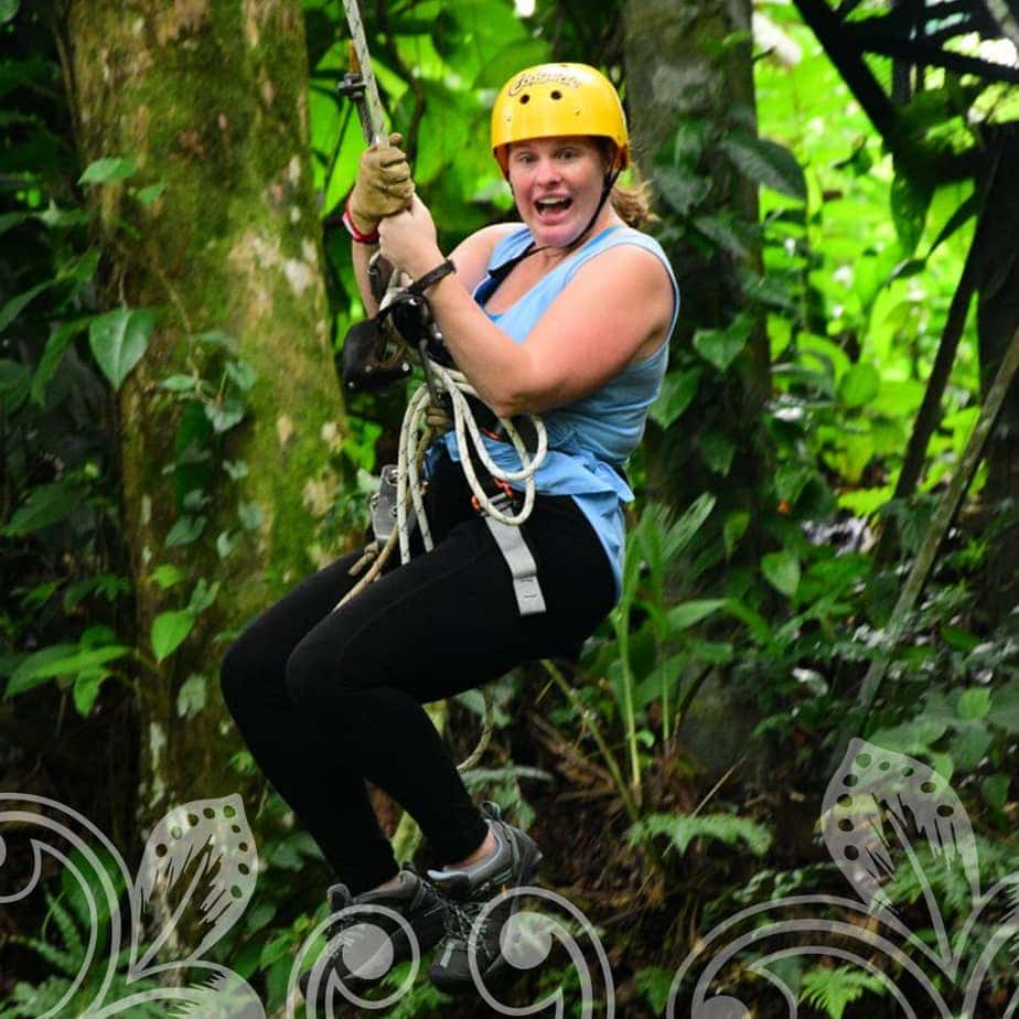 A women on a Zip line with a big smile on her face.