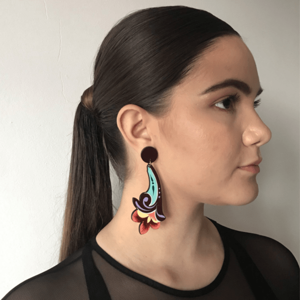 long deep color flower costa rican earring side view on woman.