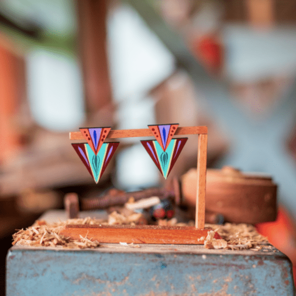 teal double triangle earrings made in costa rica displayed on wooden stand.
