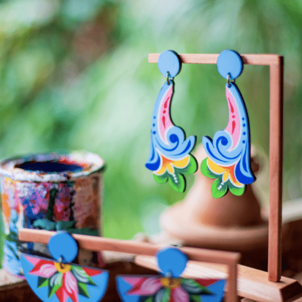 blue long flower and blue half moon costa rican earrings on wood display.