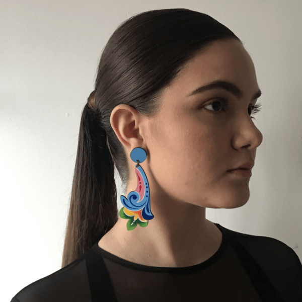 long blue costa rican flower earring side view on woman.