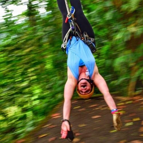 white woman ziplining upside-down.