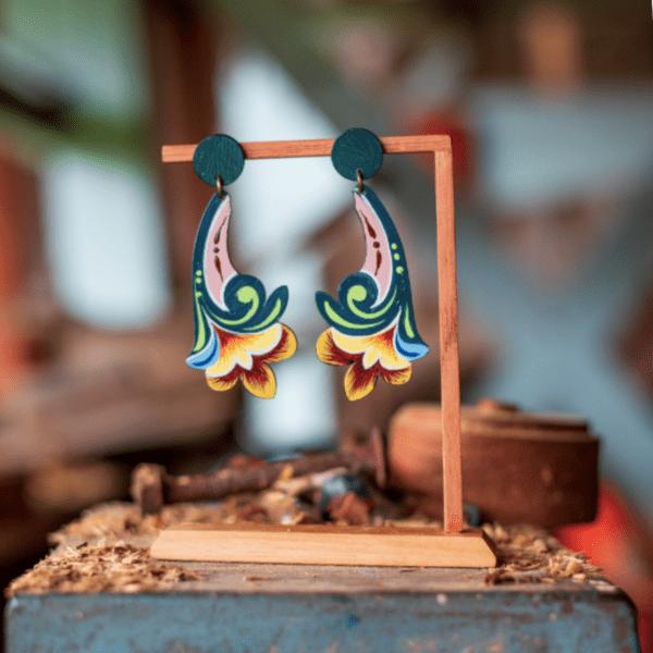 long jade flower costa rican earrings on wooden display.