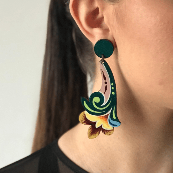 Jade long flower costa rican earring close up side view on woman.
