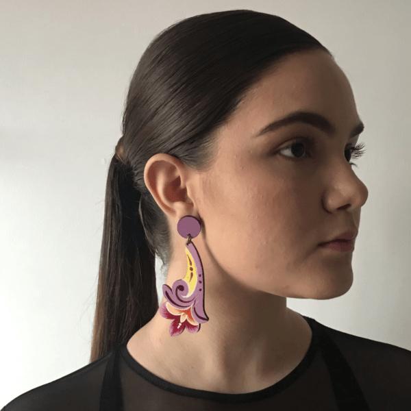 sideview of terracotta flower costa rican earring worn by woman.