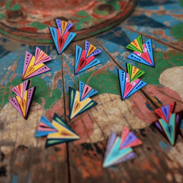 5 sets of double triangle earrings displayed on wooden tabletop in costa rica.