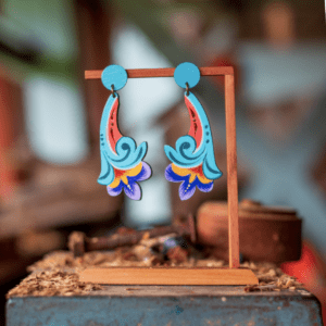 pair of turquoise flower costa rican earrings on wooden stand.