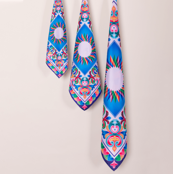 3 sizes of blue and rainbow patterned El Canto kerchief scarves hanging from wall.