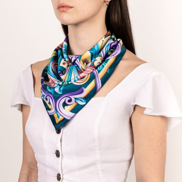 dark teal, green, blue, purple and gold El Canto kerchief worn as décolletage and neck scarf.