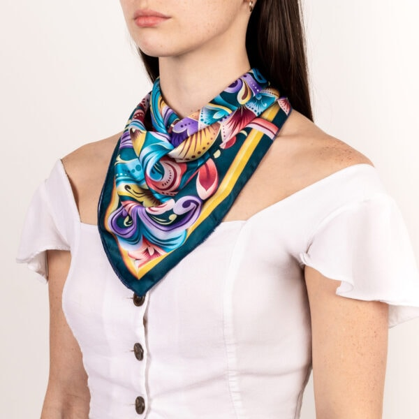 blue, purple, gold and dark teal El Canto kerchief worn as décolletage scarf .