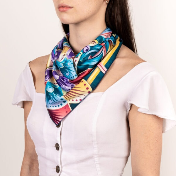 blue, purple, dark teal and gold colored and patterned El Canto kerchief worn as long décolletage accessory scarf.