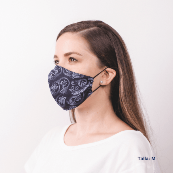 side view of woman wearing costa rican small grey facemask with white design pattern.