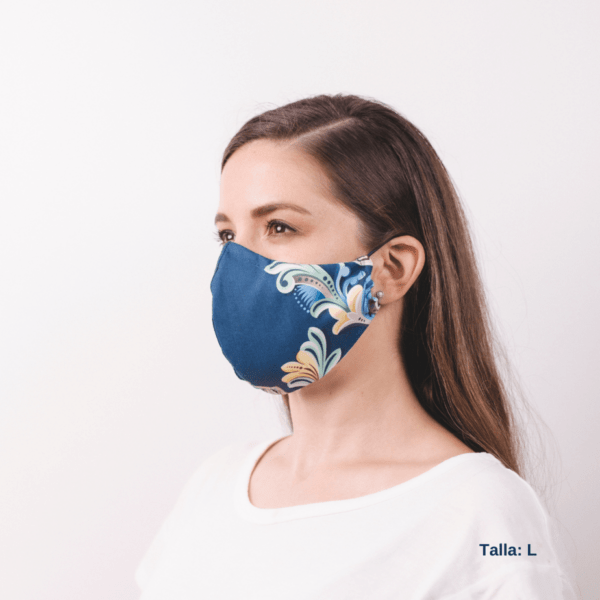 woman wearing large handmade blue costa rican facemask with floral design on side.