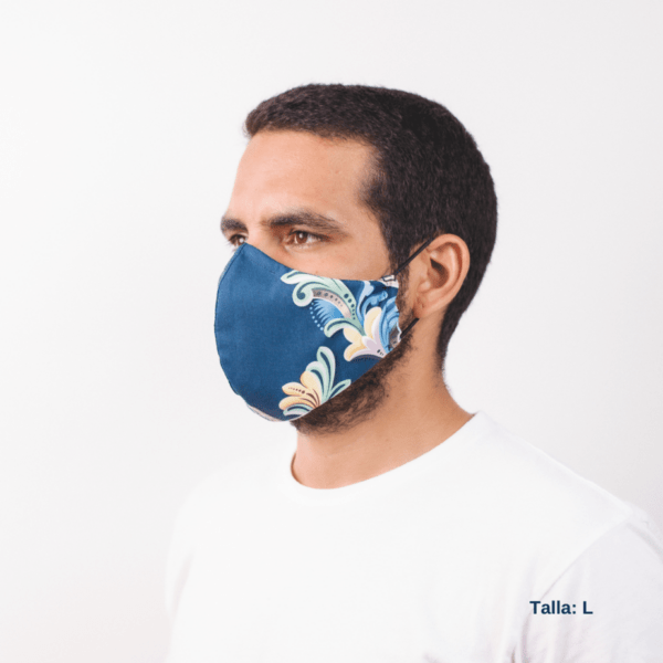 sideview of man wearing large blue facemask with costa rican designs on the side.