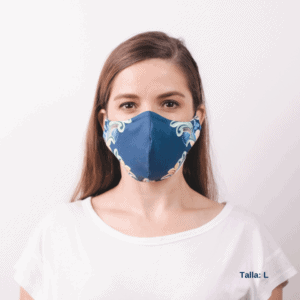 frontal view of woman wearing large blue facemask featuring costa rican designs on the side.
