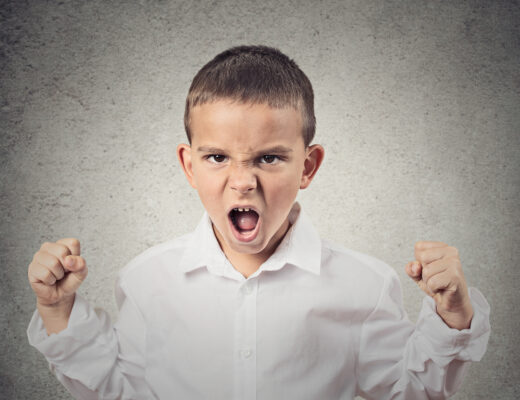 frustrated, angry and yelling boy with clenched fists