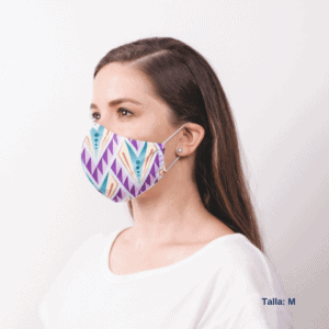 sideview of woman wearing large costa rican facemask with purple, teal and yellow designs and ear straps.