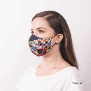 sideview of woman wearing black costa rican facemask with long ear straps and brightly colored design.