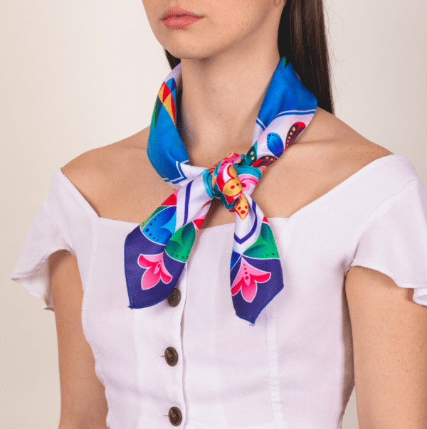 bright rainbow colored large sized El Cando kerchief worn as neck and décolletage accessory scarf.