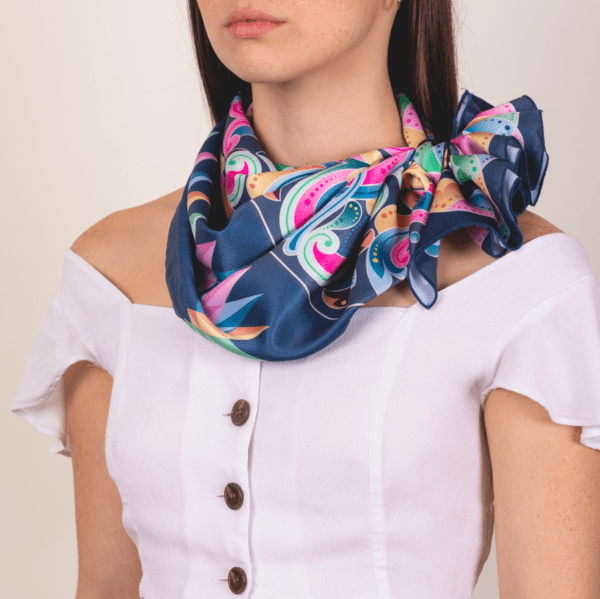 large pastel and peacock blue colored El Canto kerchief worn as frilly knotted décolletage scarf accessory.